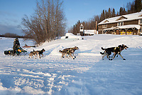 Jeff King runs up the bank of the Yukon River to Anvik during Iditarod 2009