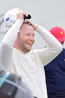 Brandon Grace (RSA) cracks up on the first tee as the International contingent sings him a song from the stands during round 3 Foursomes of the 2017 President's Cup, Liberty National Golf Club, Jersey City, New Jersey, USA. 9/30/2017.<br /> Picture: Golffile | Ken Murray<br /> <br /> All photo usage must carry mandatory copyright credit (&copy; Golffile | Ken Murray)