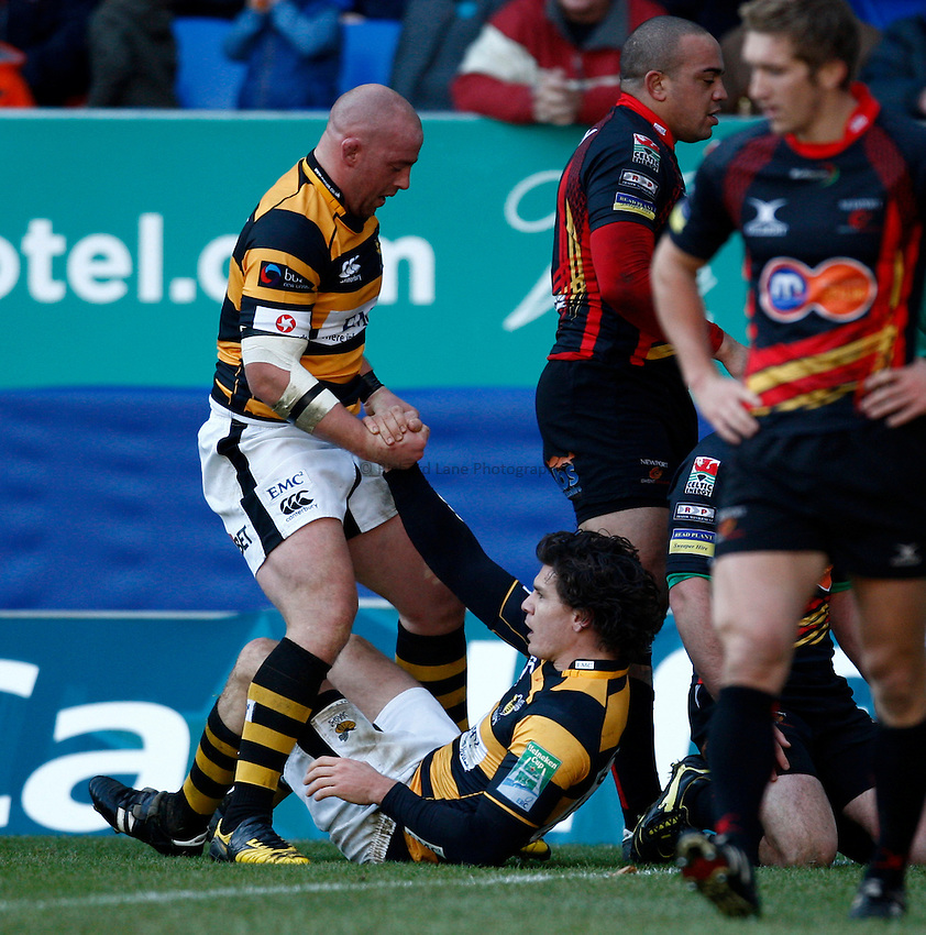 Photo: Richard Lane/Richard Lane Photography. Newport Gwent Dragons v London Wasps. Heineken Cup. 12/12/2010. Wasps' Ben Jacobs is helped up by Joe Ward after scoring a try.