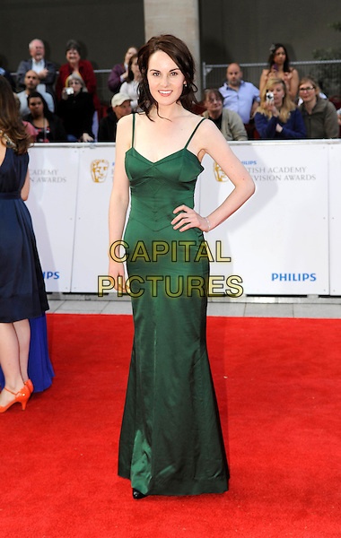 MICHELLE DOCKERY.The Philips British Academy Television Awards, Grosvenor house Hotel, Park Lane, London, England, UK..May 22nd 2011.arrivals TV Baftas Bafta full length maxi dress green silk satin hand on hip.CAP/DH.©David Hitchens/Capital Pictures.