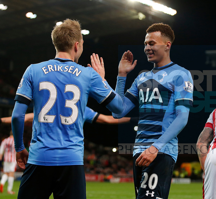 Christian Eriksen of Tottenham celebrates with scorer Dele Alli of Tottenham following the fourth goal during the Barclays Premier League match at The Britannia Stadium. Photo credit should read: Simon Bellis/Sportimage