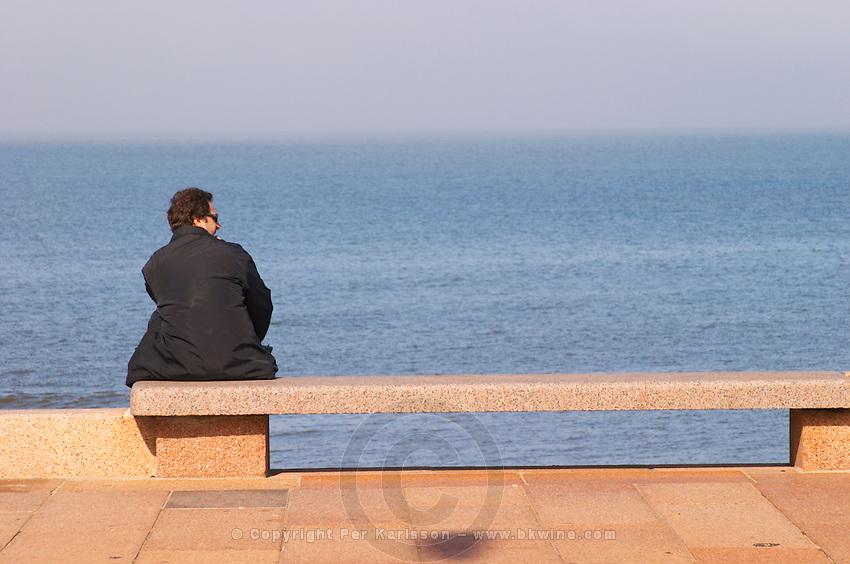 A man in black sitting on a red stone bench faxing the river sea looking right in profile, on the riverside seaside walk along the river Rio de la Plata Ramblas Sur, Gran Bretagna and Republica Argentina Montevideo, Uruguay, South America