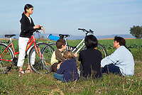 Family taking a break after biking through the countryside near the village of Ruy, Isere, France.