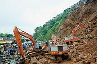 INDIA Mumbai Bombay, by landslide destroyed slum huts at rock during monsoon , search for victims  / INDIEN, Megacity Metropole Mumbai Bombay, durch Monsun abgerutschte Slumhuetten , Bagger raeumen Schutt fuer Suche nach Verschuetteten Menschen und Opfern