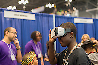 A visitor to the Comcast NBCUniversal booth wears a Samsung Gear VR Virtual reality device at a Career Expo held at the FIRST Robotics NYC Championship at the Jacob Javits Convention Center in New York on Sunday, March 13, 2016. The expo enables participants to speak with companies and professional organizations giving a real-world look into science and technology as used in the business world and their career opportunities. (© Richard B. Levine)