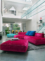 Key pieces in the living room include a vibrant pink sofa and matching ottoman, as well as an aquamarine blue ottoman for contrast