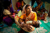 An elder Indian woman holds her malnourished grand-child at a Nutrition Rehabilitation Centre in the Purulia district of the Eastern Indian state of West Bengal on the 29th of March 2011.