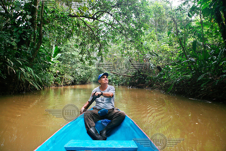 Guide Don Chico on his boat in the Tortuguero National Park. He used to be a farmer in this area until the Park autority bought his land in order to protect its wildlife. The park extents along the Caribbean coast for 22 km from Jaloba to Tortuguero. It has 11 ecological habitats, from high rainforest to marsh communities. A maze of channels, streams and swamps are home to more than 300 bird species...
