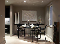 A pair of obelisks and a candelabra flank a plaster relief in this dining area which is furnished with black Philippe Starck Ghost Chairs