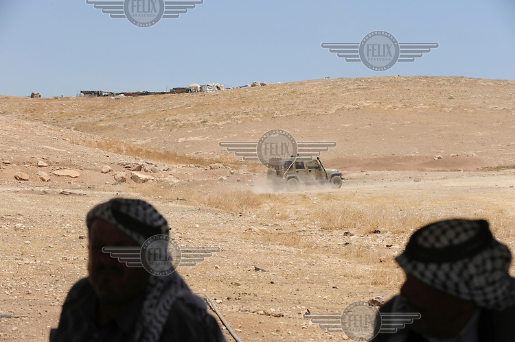 An Israeli army jeep drives past as a group of Bedouin men gather in a hosting tent to discuss problems they face living in an encampment in Hadidyeh in the Jordan Valley. The Bedouin living here have been issued with eviction orders by Israeli authorities...
