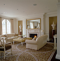 A room in perfect symmetry with matching sofas and a pair of pedestal-mounted urns flanking the 18th-century-style fireplace