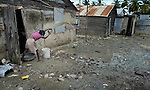 A girl throws out household waste in Batey Bombita, a community in the southwest of the Dominican Republic whose population is composed of Haitian immigrants and their descendents.