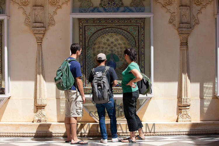 Western tourists in Mor Chowk, Peacock Courtyard in the Zenana Mahal of The City Palace of Maharana of Udaipur, Rajasthan, India