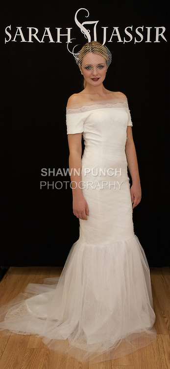 """Model poses in """"Muse"""" - a ruched off the shoulder Chantilly lace mermaid gown with tulle overlay, from the Sarah Jassir Fall 2013: From Concept To Creation collection, for her Angelique Bridal store opening at 6 East 45 Street, during New York Bridal Fashion Week, October 15, 2012"""