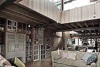 The open plan second floor houses the kitchen, dining area and living room. The ceiling was removed to let in more light, and windows and doors from the original factory have been recycled to make bookcases and cupboards