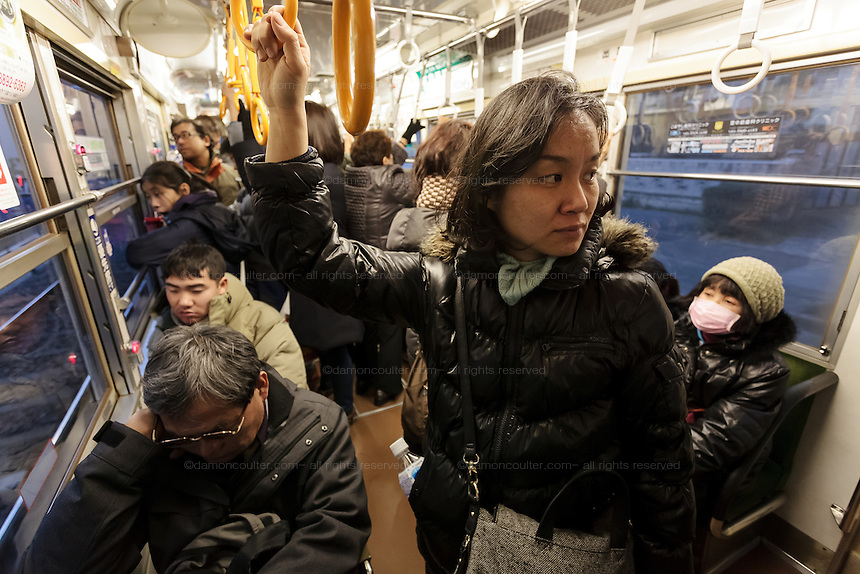 Passengers ride a street car or tram on the Toden Arakawa Line in Tokyo, Japan. Sunday February 15th 2015. The line is nick-named the Chin-chin Densha and is the last remaining tram line in Japan's capital city.