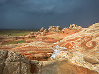 White Pocket in the Vermilion Cliffs of Northern Arizona has become a favorite photography place of refuge for me.  I'll only travel here after a rain storm.  The approaching storm or clearing offers the best opportunities for photographs.  Here I was out in a severe but brief rain storm, watching the water run down the sandstone cliffs and forming many streams that were very short lived.  Despite an umbrella, I was totally drenched.