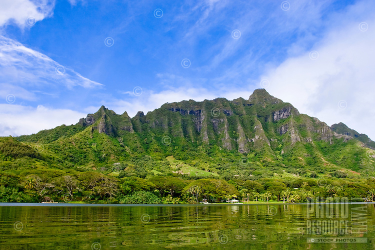 The lush green Kualoa mountain range is set off by reflecting waters and bright blue sky.