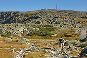 Hiker on the Appalachian Trail (Gulfside Trail) in the White Mountains, New Hampshire. Mount Washington is in the background. The Great Gulf is on the left out of view.