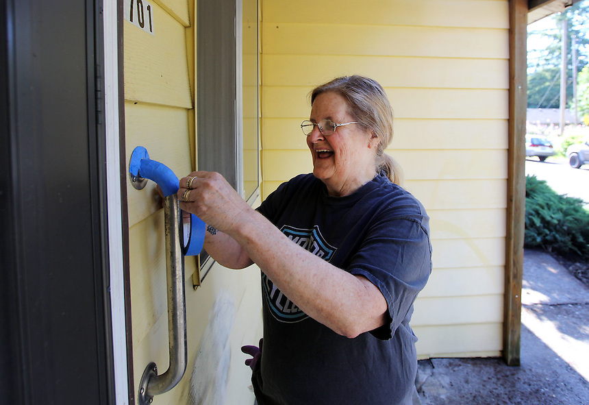 Cynthia Powers of the Maplewood Neighborhood Association helps an elderly neighbor with home maintenance in Vancouver Friday June 25, 2016. (Photo by Natalie Behring for the Columbian)