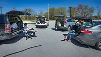 Tripp Hollowell (from left), Shannon Suttie, Ginger Macfarlan and Lindsay Letterle hold a team meeting Wednesday, March 25, 2020, in the parking lot at The Clorox Company office in Bentonville. The Clorox employees have been working from home, but wanted to take advantage of the nice weather to meet in person while still practicing good social distancing to prevent the spread of the covid-19 pandemic. Go to nwaonline.com/photos to see more photos.<br /> (NWA Democrat-Gazette/Ben Goff)