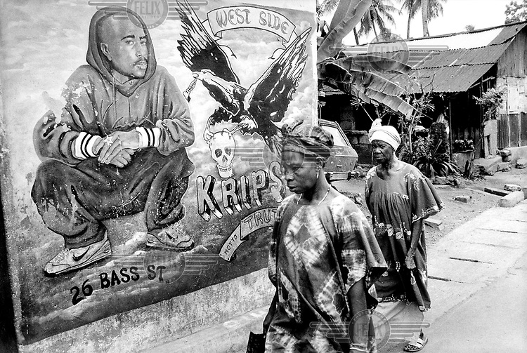Women walking by mural of rapper Tupac Shakur in Brookfields district of Freetown. Gangsta Rapper Tupac is said to be an icon for the RUF rebels. Sierra Leone...© Teun Voeten/Panos