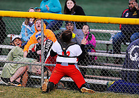 Fauquier catcher Angelle Marshall traps a foul ball against the fence with her face as spectators react to the unusual play.