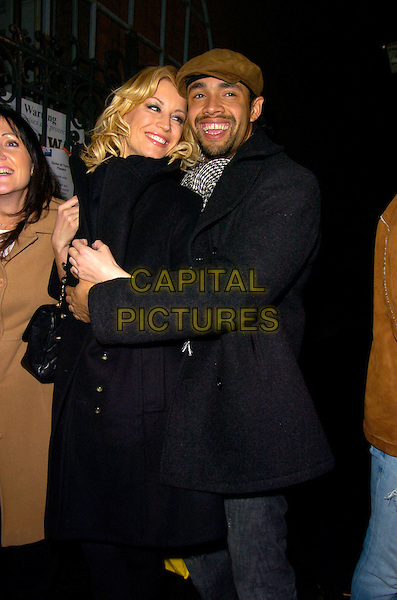 "DENISE VAN OUTEN & LEON LOPEZ.Denise Van Outen's final ""Rent"" performance, Duke of York Theatre, London, England..December 22nd, 2007.half length black coat jacket scarf striped stripes top buttons hug embrace brown hat beard facial hair .CAP/CAN.©Can Nguyen/Capital Pictures"