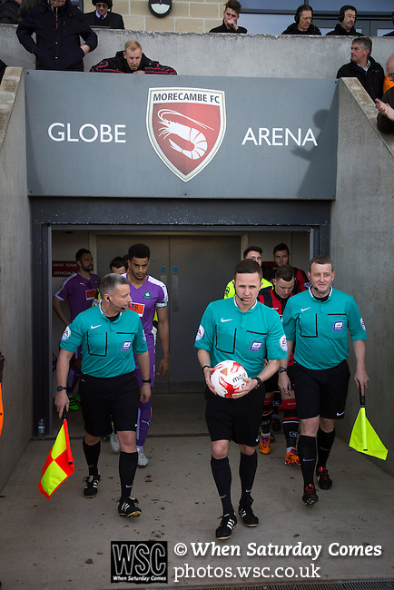 Morecambe 0 Plymouth Argyle 2, 25/03/2016. Globe Arena, League 2. Referee David Webb leading out the teams at the Globe Arena before Morecambe (in red stripes) hosted Plymouth Argyle in a League 2 fixture. The stadium was opened in 2010 and replaced Morecambe's traditional home of Christie Park which had been their home since 1921, the year after their foundation. Plymouth won this fixture by 2-0 watched by 2,081 spectators, in a game delayed by 30 minutes due to traffic congestion affecting travelling Argyle fans.  Photo by Colin McPherson.