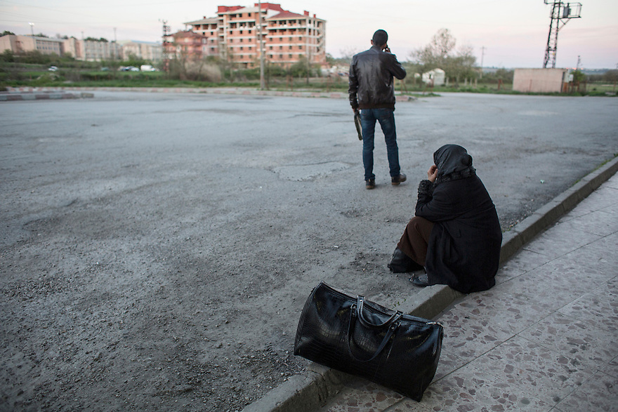 EDIRNE, TURKEY--  A woman waits with her luggage outside the bus station in Edirne. Migrants arrive to the border city of Edirne everyday in order to try to cross into Bulgaria.
