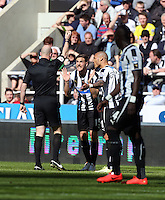 Pictured: Dan Gosling of Newcastle (C) is protesting to the match referee Anthony Taylor (L) for the yellow card being shown for the former's foul on Wayne Routledge of Swansea. Saturday 19 April 2014<br />