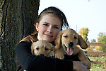 Teenaged girl with golden retriever puppy(ies)