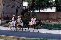Pakistan  Peshawar  1986..Pakistani donkey owners ride through a street