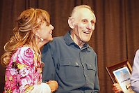 Thursday February 28, 2013  Longtime Skwentna checker Joe Delia is all smiles as he stands with DeeDee Jonrowe and is presented, along with his wife Norma, with the Iditarod Trail Founders Award at the musher drawing banquet held at the Dena'ina Convention Center in Anchorage two days prior to the start of Iditarod 2013...Photo (C) Jeff Schultz/IditarodPhotos.com  Do not reproduce without permission.