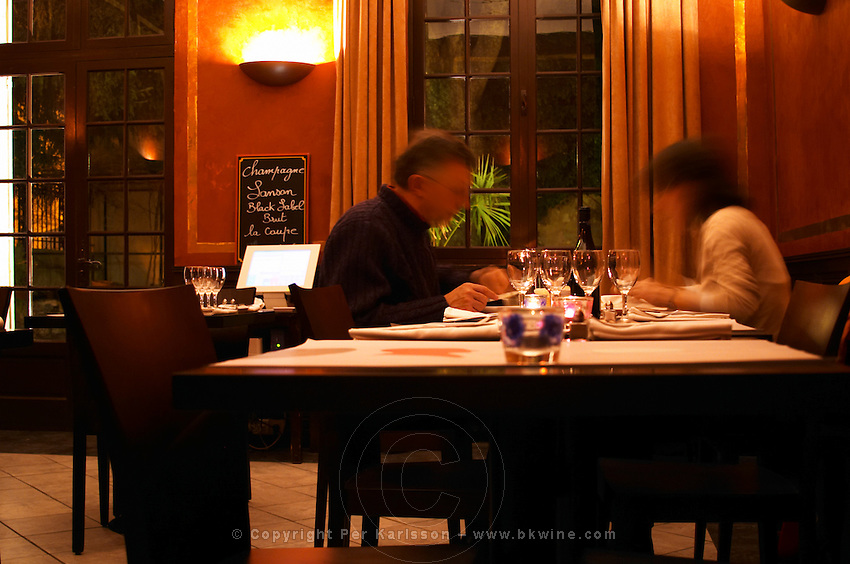 Inside the restaurant Le Mornet. A couple (blurred) sitting eating in candle light, glasses on the table a signboard advertising today's champagne offer.  Avignon, Vaucluse, Provence, Alpes Cote d Azur, France, Europe