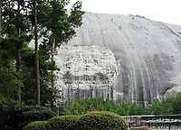 Stock photo: Stone mountain carving of the historical figures as seen from the audience viewing terrace and beautiful trees in the foreground.