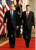 Washington, DC - September 29, 2005 -- United States President George W. Bush, left, and John Glover Roberts, Jr., right, walk through the Cross Hall to the East Room of the White House in Washington, D.C. on September 29, 2005 where Roberts took the oath as the 17th Chief Justice of the United States..Credit: Ron Sachs / CNP
