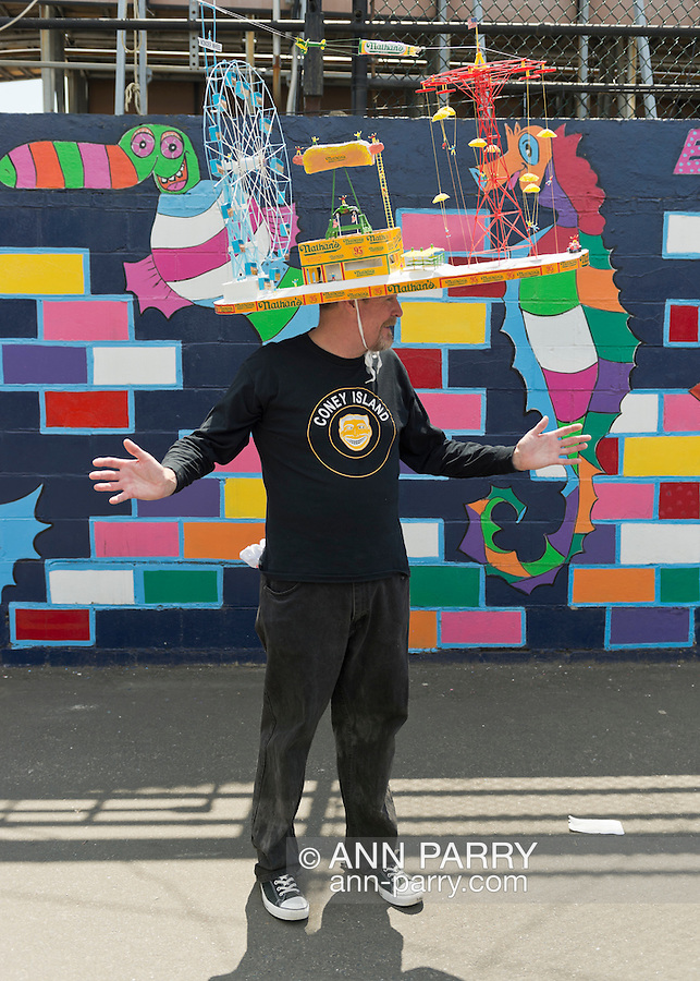 Brooklyn, New York, U.S. - August 9, 2014 - BRIAN DILLON of Bay Ridge is wearing a large handmade Coney Island themed hat with a Wonder Wheel, Nathan's Famous, and red Parachute Jump ride, at the Fourth Annual History Day at Deno's Wonder Wheel Amusement Park and The Coney Island History Project, has family fun music, history, and entertainment at historic Coney Island. The theme of this year's festivities was the return of the Astroland Rocket.