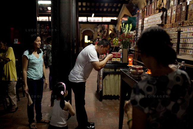 Nathan Nguyen, right, from Seattle, Washington, USA, prays with his wife Thuy Hang, left, and their daughter Natalie, 2, for Thuy Hang's father who recently died.  Photo taken at the Giac Lam Pagoda in Tan Binh District in Ho Chi Minh City, Vietnam. Photo taken Tuesday, May 4, 2010...Kevin German / LUCEO