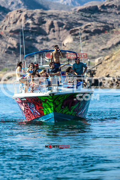 Teenage vacationers enjoy a sunny day, ride a yacht through the bay and beach of San Carlos, in the Gulf of California of the state of Sonora Mexico.<br />
