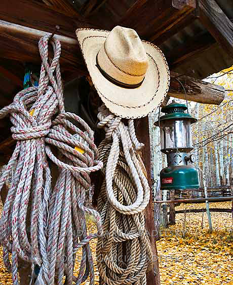Coiled lash ropes, cowboy hat and lantern hanging in the Stockyard at Bishop Canyon. Eastern Sierra, California