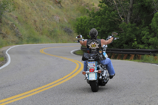 Hispanic male biker on a Harley-Davidson motorcycle (chopper) riding on Lookout Mountain Road west of Denver, Colorado, USA .  John leads private photo tours in Boulder and throughout Colorado. Year-round.
