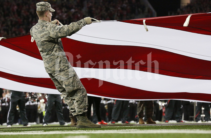 A giant Stars and Stripes is stretched out before the start of  an NCAA football game between the Ohio State Buckeyes and the Minnesota Golden Gophers at Ohio Stadium on Saturday, November 7, 2015. (Columbus Dispatch photo by Fred Squillante)