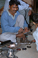 A street cobbler in New Delhi, India repairing shoes.