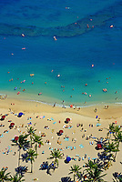Aerial shot of world famous Waikiki beach, dotted with tourists enjoying the sand, surf and palm tress.
