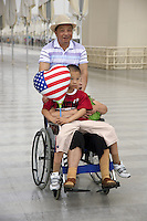 China. Shanghai. World Expo. Expo 2010 Shanghai China.   A family, all chinese tourists, during their visit. The wife is disabled and seats in a wheelchair. Her husband pushes her while their young single son seats on his mother's legs. The child holds an inflated balloon with a heart shape and the american flag. 25.06.10 © 2010 Didier Ruef