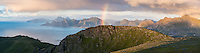 Rainbow rises from mountain landscape viewed from Ryten, Lofoten Islands, Norway