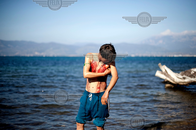 Greece/Patras/Nov 25,2012.An unaccompanied minor from Afghanistan washing himself in the sea, after the celebration of Ashura held in a makeshift camp in Patras. Hundreds of Afghans are trapped in the port of Patras living under miserable conditions with the aim to continue their journey in Europe.Giorgos Moutafis