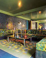 Long, elegant banquettes in the green room, their square, geometric upholstery echoing the square tiling that clads the walls. A wall to wall mirror creates the illusion of the room extending further