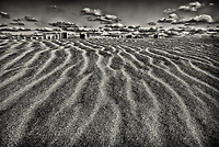 Landscape of dunes with ripples, fence tips and clouds in Outer Banks of North Carolina